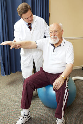 doctor_with_senior_man_in_rehab_on_ball_assisted_living_houston_tx