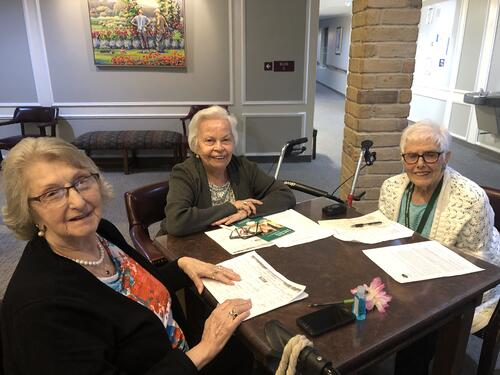 3 ladies doing puzzles at senior livng houston